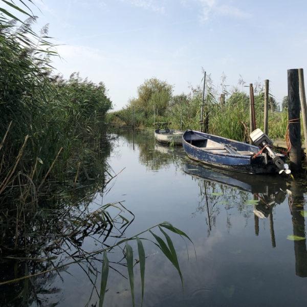 Twee bootjes in het water langs een houten kade