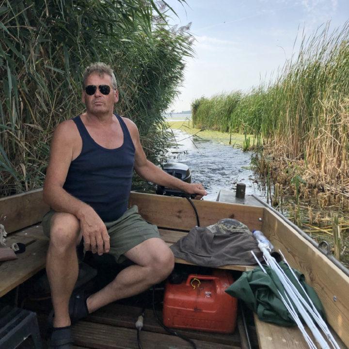 Een man met korte broek en een hemd bestuurd het bootje