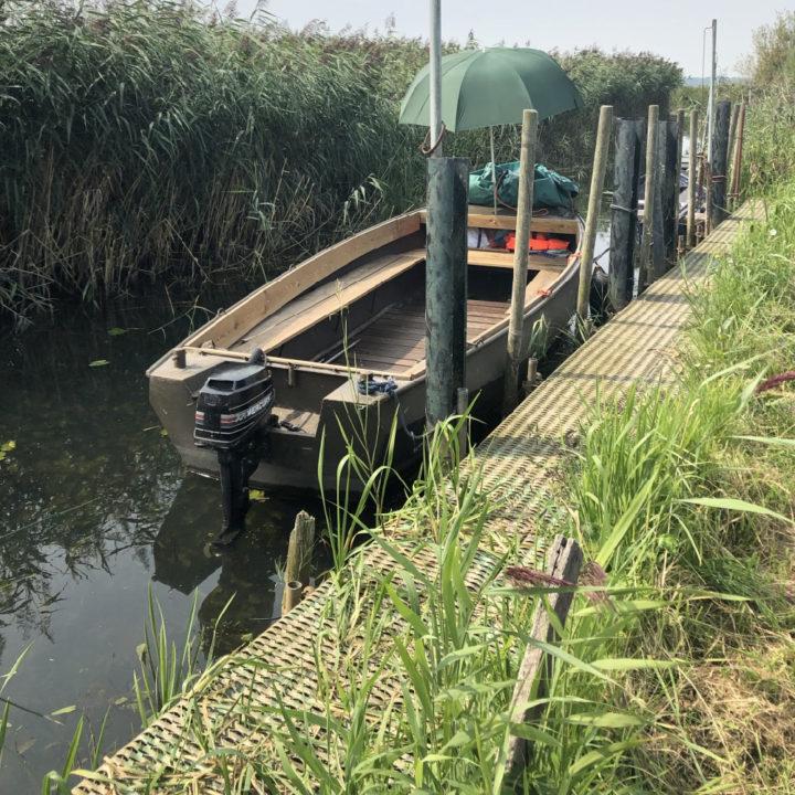 Een bootje in het water met hoog gras aan beide kanten