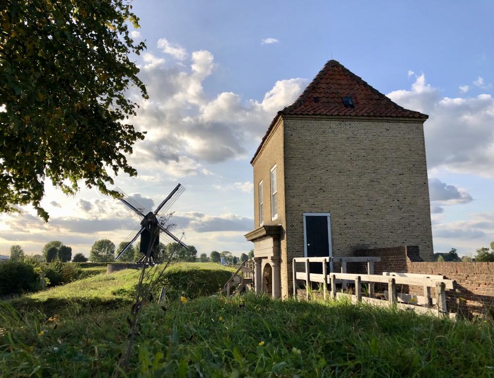 Een alleenstaand huisje op een zonnige dag met een windmolen op de achtergrond