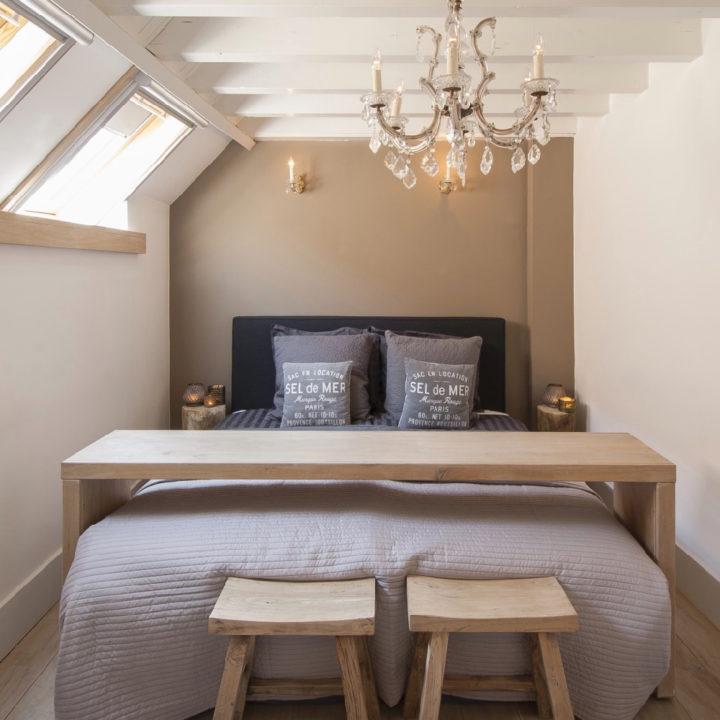 Een opgemaakt bed met een houten plank er boven dat als kastje gebruikt kan worden