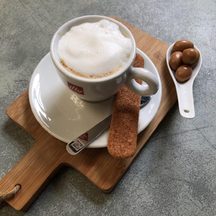 Een kopje koffie met een koekje op een houten plank