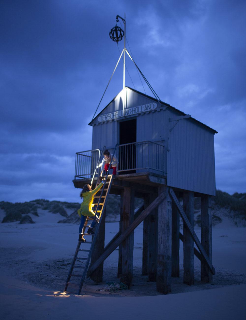 Een meisje beklimpt een ladder richting een huisje op het strand
