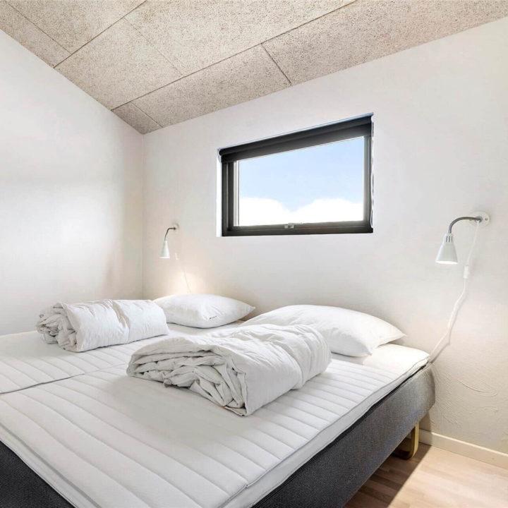Een opgemaakt bed met een open raam in de muur waar het tegen aan staat