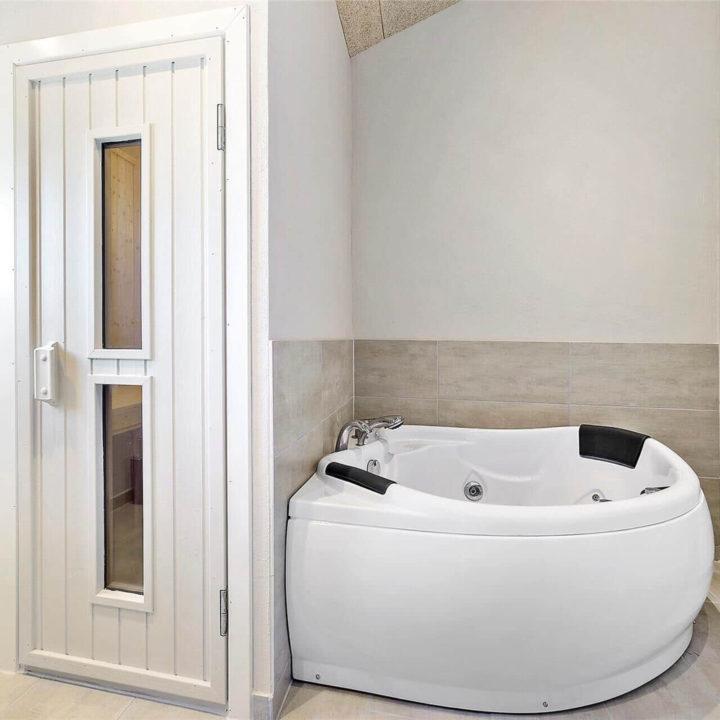 Een bad in de badkamer met een houten deur waar twee glazen in zitten