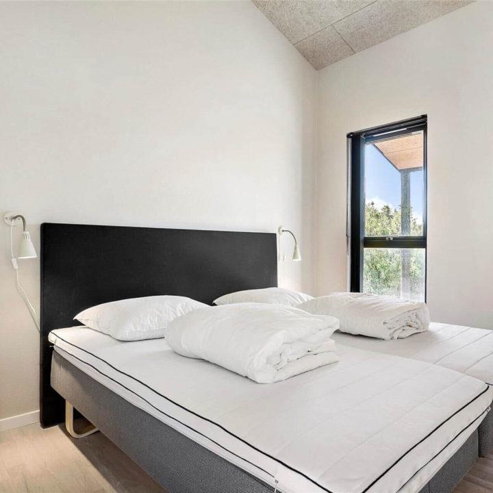 Een opgemaakt bed met een zwarte achterkant in een lichte kamer op een zonnige dagen