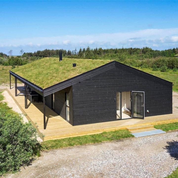 Een zwart huisje met een dak van gras en een houten terras in een open veld, met een pad van grind er voor