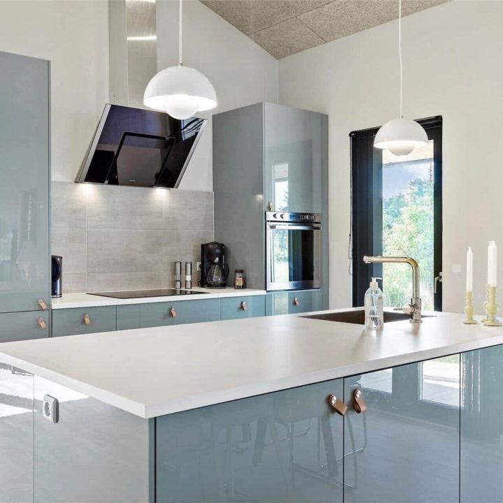 Een glanzende, lichte keuken met een koelkast, en blauwe kastjes