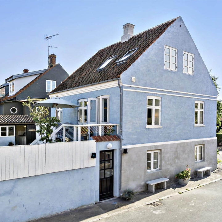 Een huisje met bluawe muren en een blauw hek