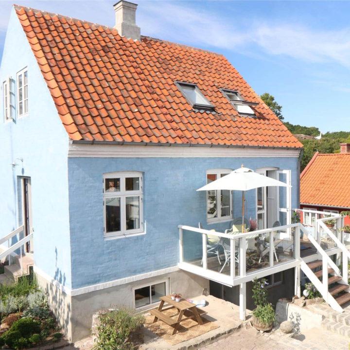 Een huis met blauwe muren, een oranje dak en een houten terras