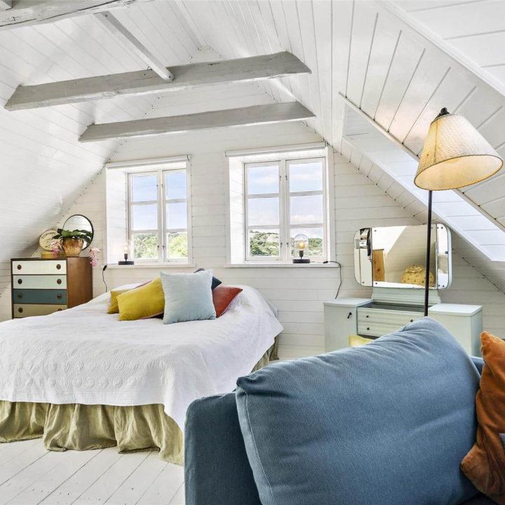 Een opgemaakt bed met gekleurde kussens in het midden van het bed. Achter het bed zijn 2 ramen