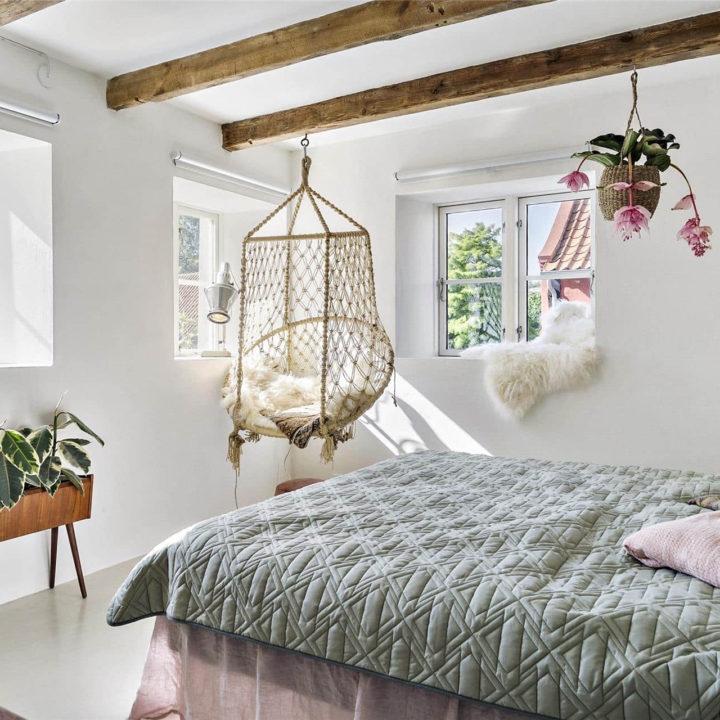 Een opgemaakt bed. In de hoek van de kamer hangt een stoel