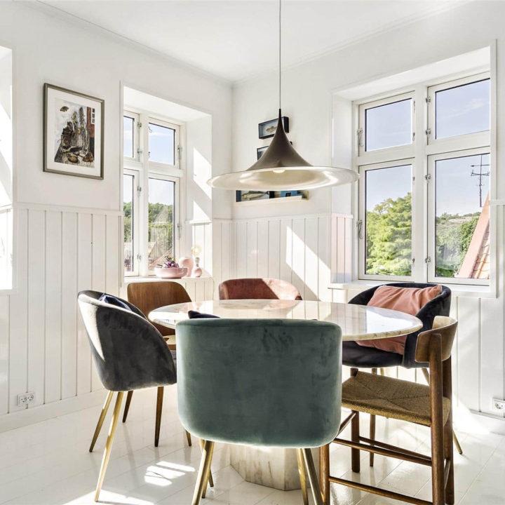 Een witte ronde tafel omringd door 6 stoelen in de hoek van de kamer