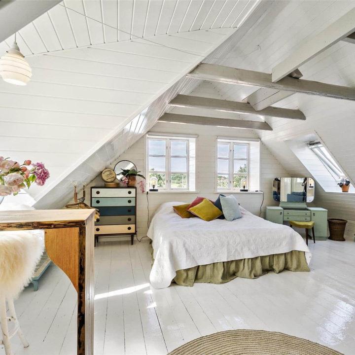 Een opgemaakt bed met kussens in het midden in een lichte kamer met open ramen