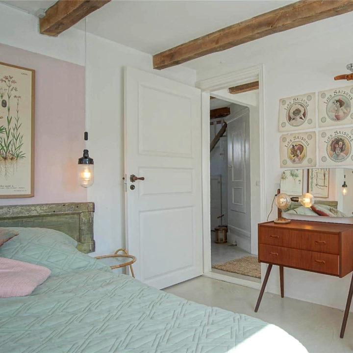 Een opgemaakt bed met lichtgroene dekens met een open deur richting de gang