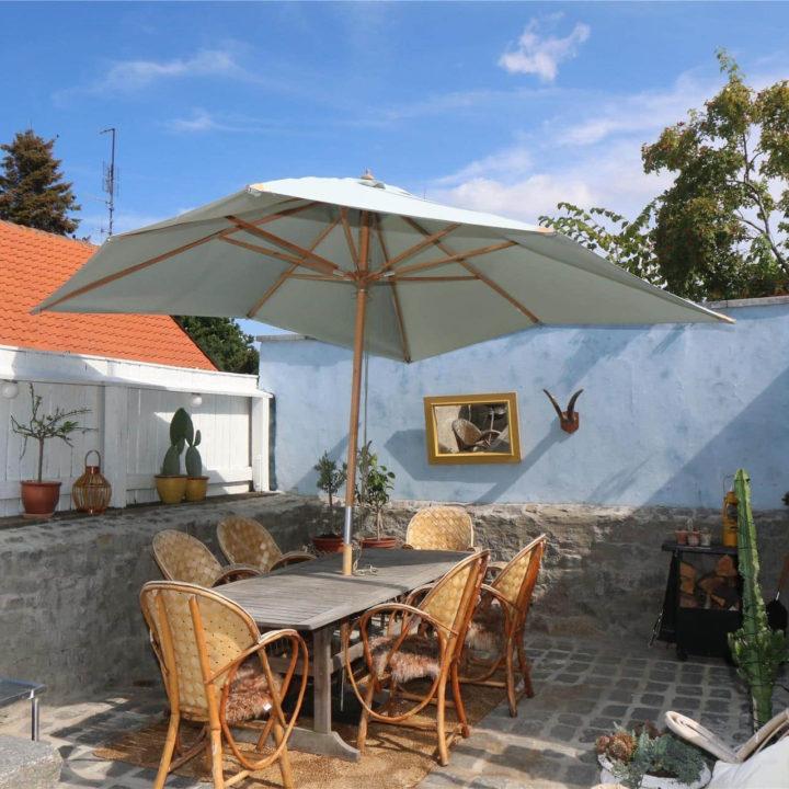 Een tafel in de tuin met 6 stoelen voor een blauwe muur