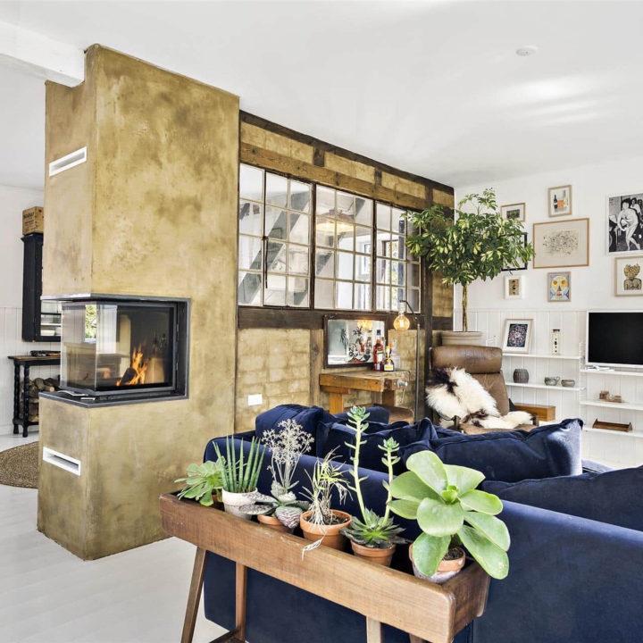 Een blauwe bank met een bakje planten er achter. Naast de bank is een gele muur met ramen met uitzicht op de rest van de kamer