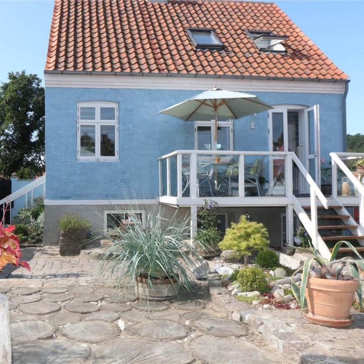 Een blauw huisje met oranje dak en een verhoogd houten terras