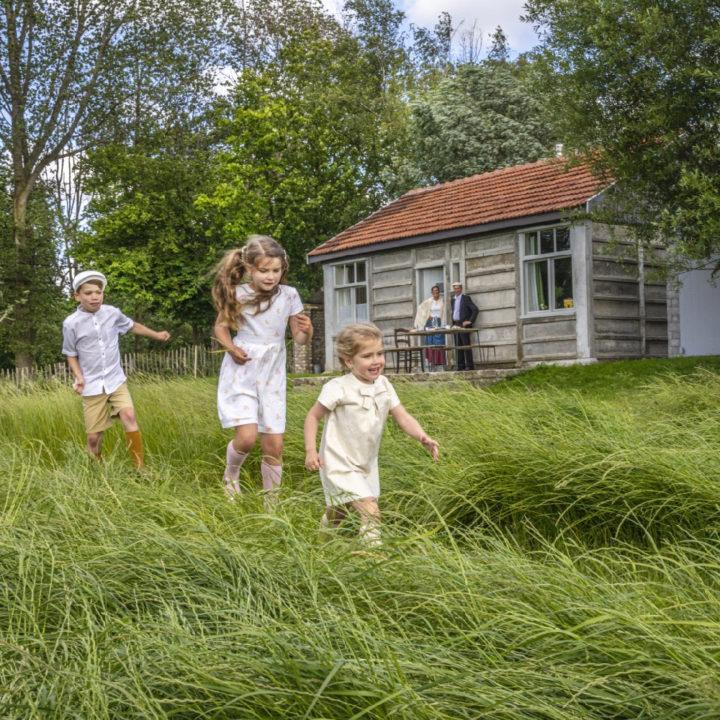Rennende kinderen in het gras bij een vakantiehuis
