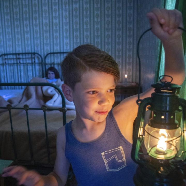 Jongetje met olielamp in een slaapkamer van een vakantiehuis