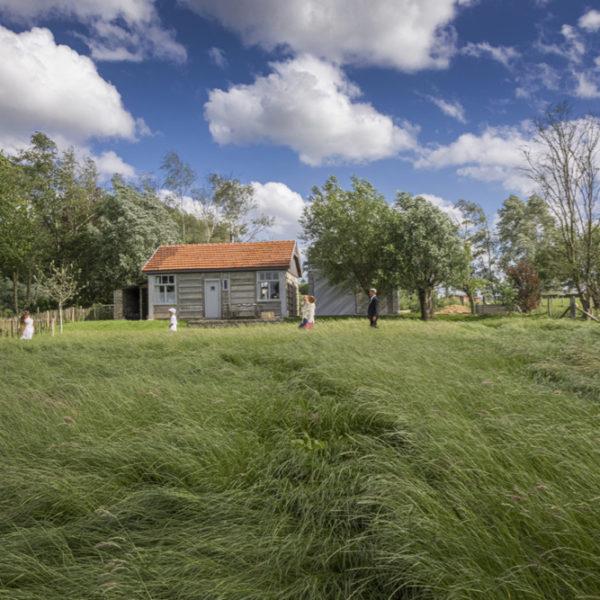 Houten barak met een groot grasveld ervoor