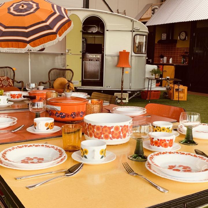 Gedekte tafel op de indoorcamping met een caravan op de achtergrond