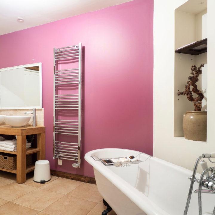 Roze badkamerwand met vrijstaand bad