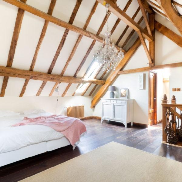 Ruime slaapkamer met veel wit en stoere balken