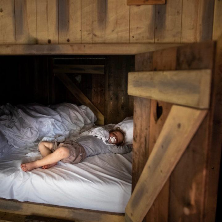 Kindje ligt te slapen in een bedstee