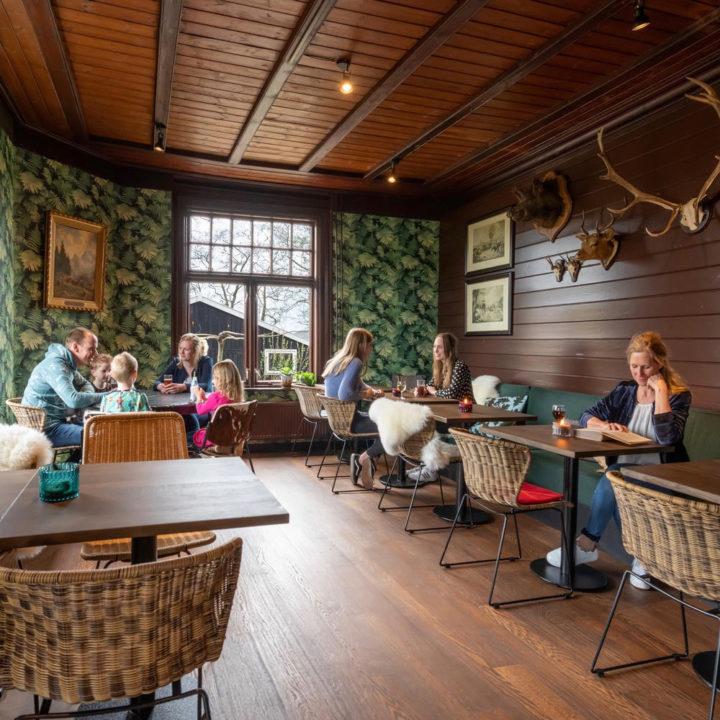 Restaurant met donkere houten muren, een gewei, bontjes op stoelen