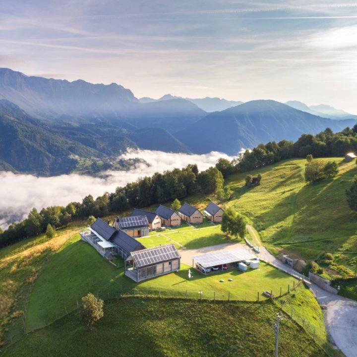 Meerdere huizen bij elkaar in een groene omgeving met uitzicht op de bergen