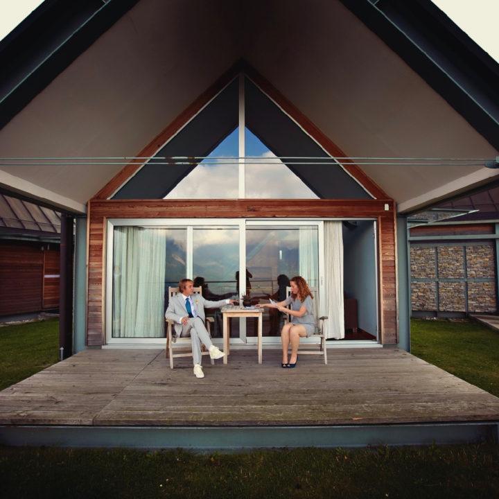 Mensen op een terras voor een huisje