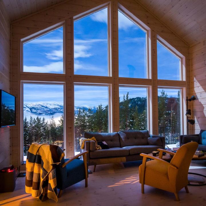 Woonkamer voor grote glazen gevel met zicht op besneeuwde heuvels