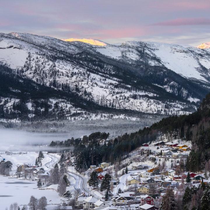 Dal met Noorse huizen in de sneeuw