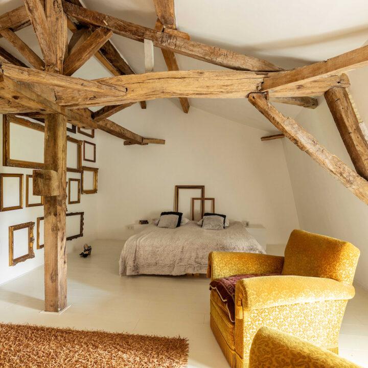 Slaapkamer met houten gebinten en lege houten lijstjes aan de muur