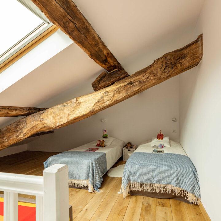 Twee eenpersoonsbedden onder de houten balken
