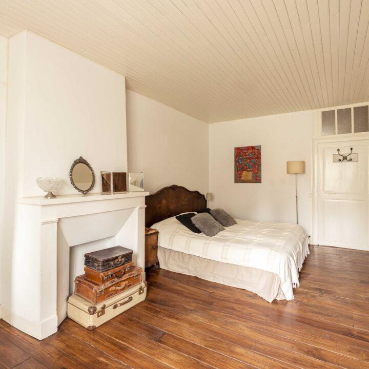 Slaapkamer met tweepersoons bed en stapeltje koffers
