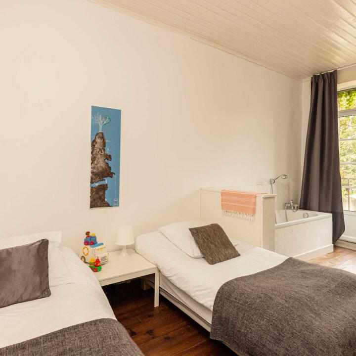 Slaapkamer met twee eenpersoonsbedden en ligbad