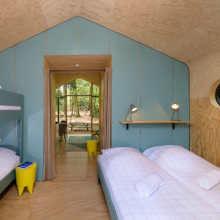 Slaapkamer met opgemaakte bedden en open doorgang naar de woonkamer
