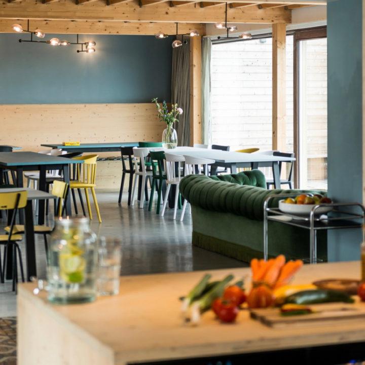 Lichte eetkamer met blauwe wand met meerdere tafels en gekleurde stoelen