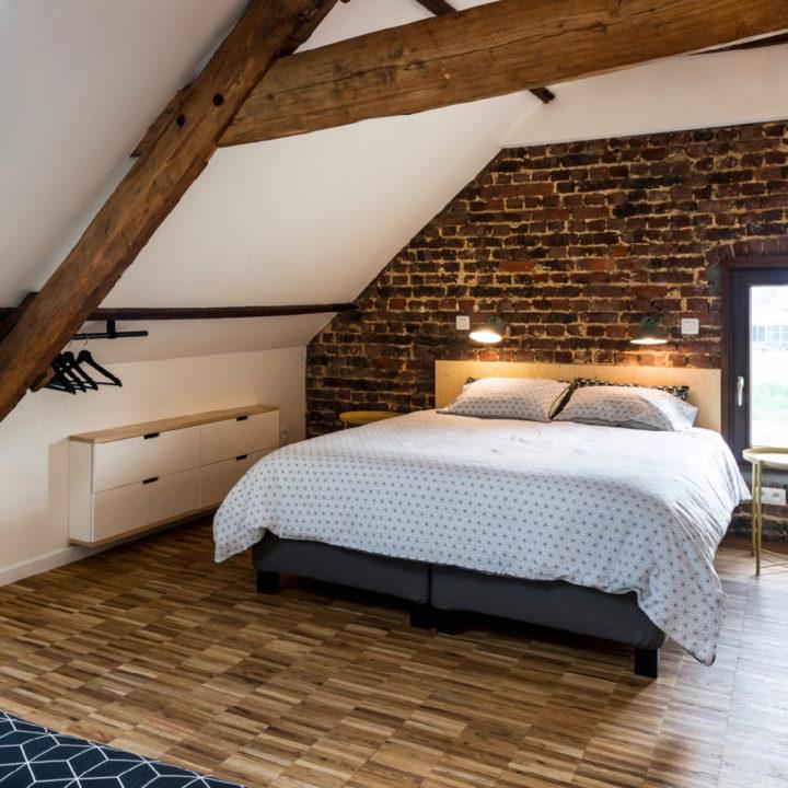 Slaapkamer met stoere balken en een tweepersoons bed