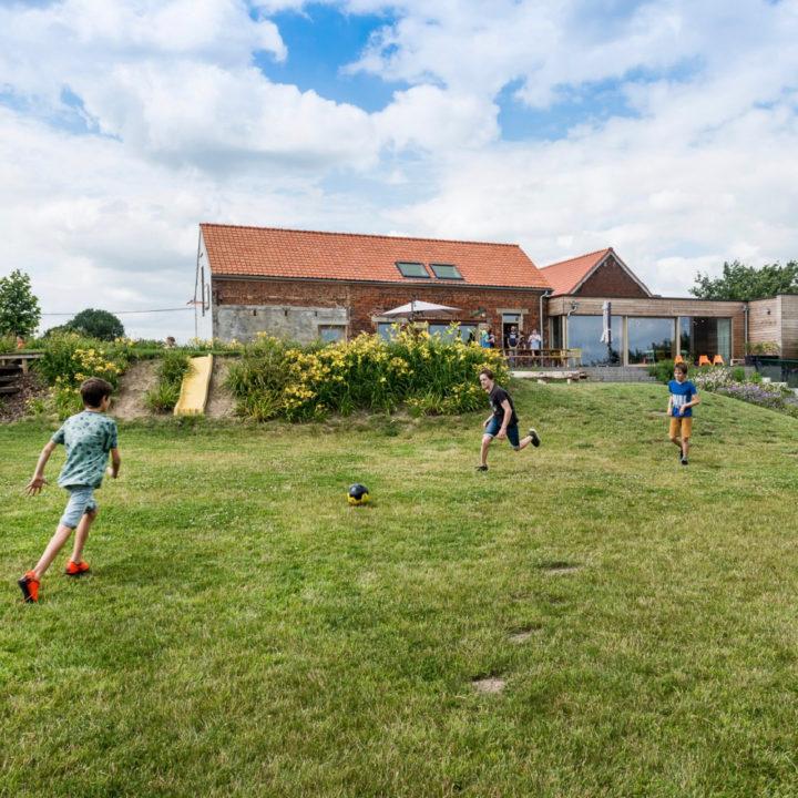 Voetballende jongeren op het grasveld