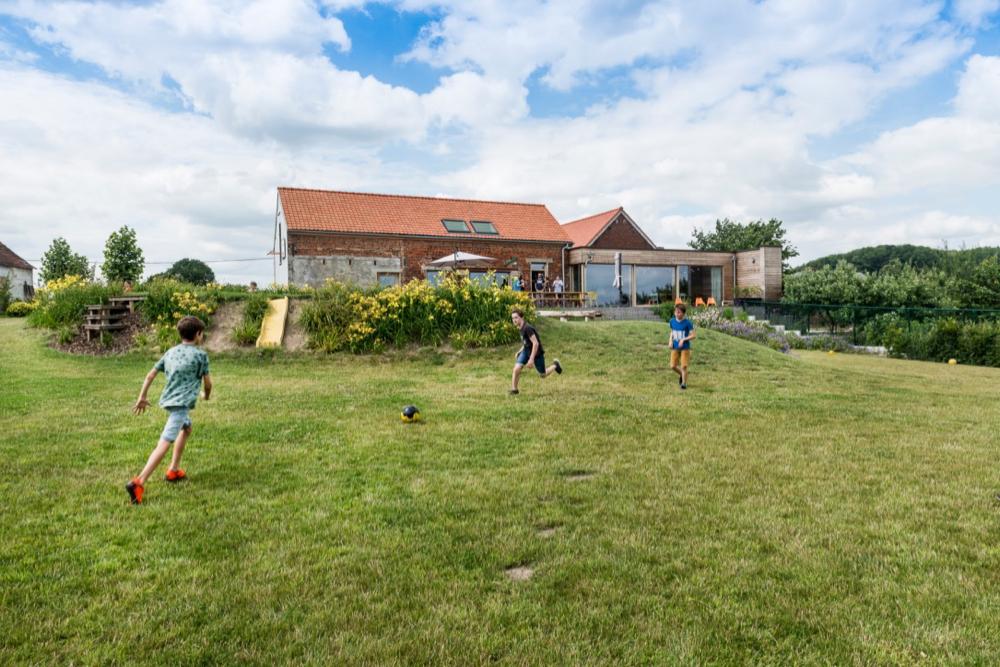 Groepshuis met grasveld met voetballende jongeren