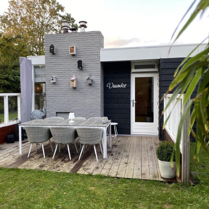 Vakantiebungalow met grijze muur en terras met 6 stoelen