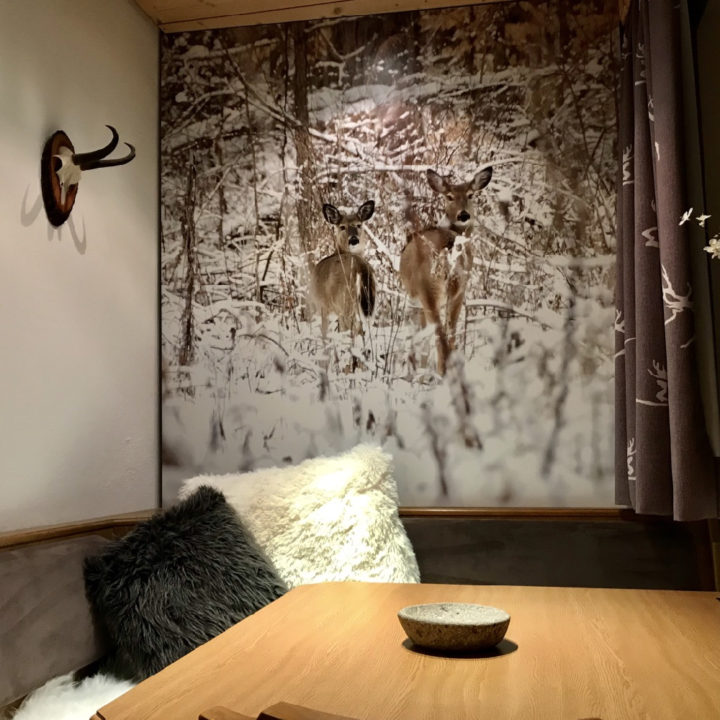 Eethoek met kussens en foto van hertjes in de sneeuw aan de muur