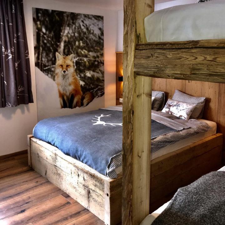 Familiekamer met stapelbed en stoer houten bed