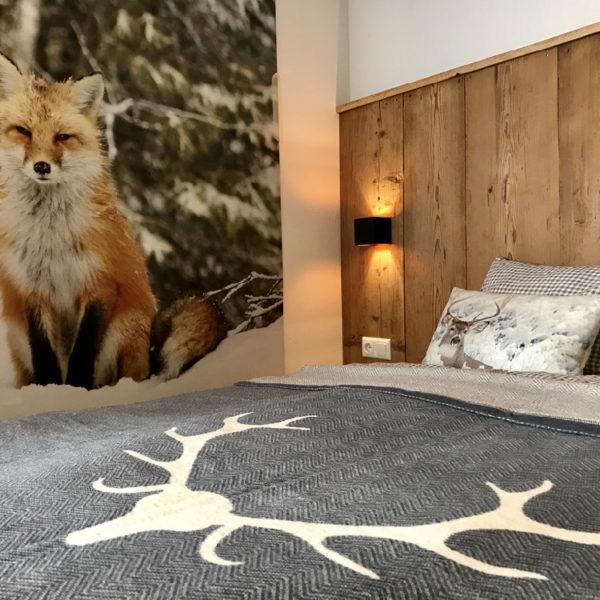 Close up van een bed met houten achterwand, en een metersgrote foto van een vos aan de muur
