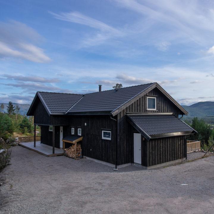 Zwart houten vakantiehuis op de heuvels in Noorwegen