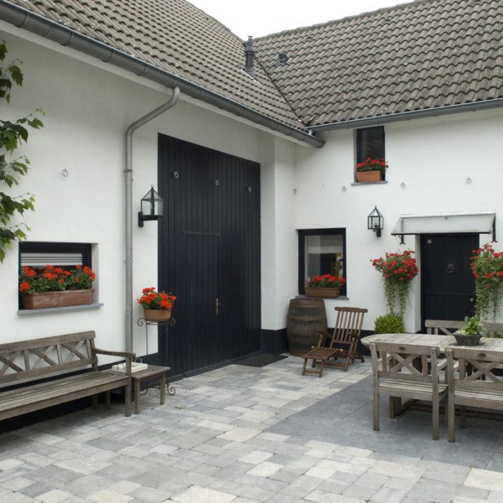 Binnenplaats van een hoeve met geraniums aan de muur