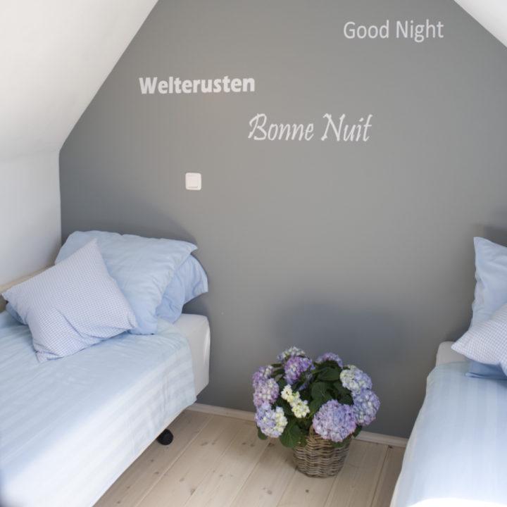 Slaapkamer met grijze wand met teksten slaap lekker in verschillende talen